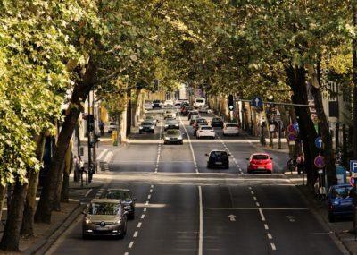 Vierspurige Straße mit Autos umrahmt von Bäumen